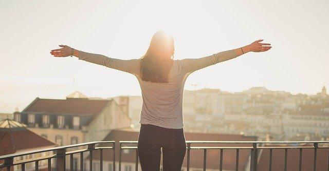 žena na balkonu bytu s rozpaženými rukami