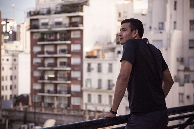 muž vyhlížející z balkonu bytu
